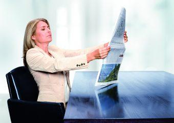 Frau mit Alterssichtigkeit liest Zeitung