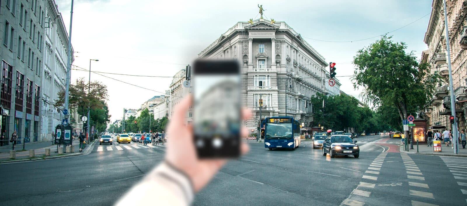 Innenstadt mit unscharfem Handy im Vordergrund